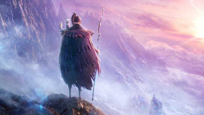 A man stands with his back to the camera over a great colorful precipice as the sun sets in the distance. A small animal resides on his shoulder and the man is carrying a staff.