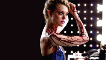 Jesse looks in the mirror at a shoot. She is wearing a dark blue dress and there is fake blood on her skin