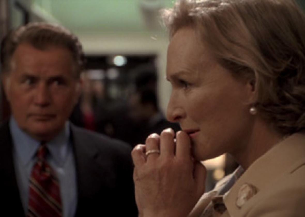 Glenn Close as Evelyn Baker Lang in The Supremes stands with her hands to her mouth deep in thought as President Bartlet stands out of focus to the right.