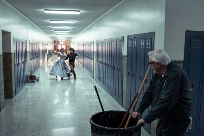 A pair of dancers perform in front of a school janitor.