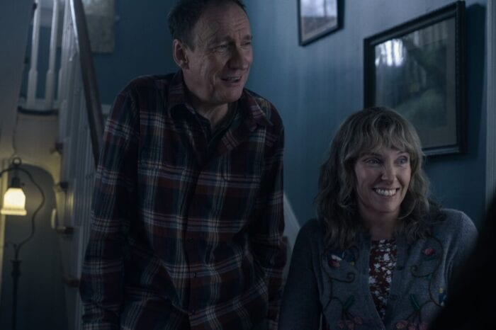 Jake's mother and father smile at meeting his girlfriend.