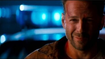 Bruce Willis smiling in front of police cars