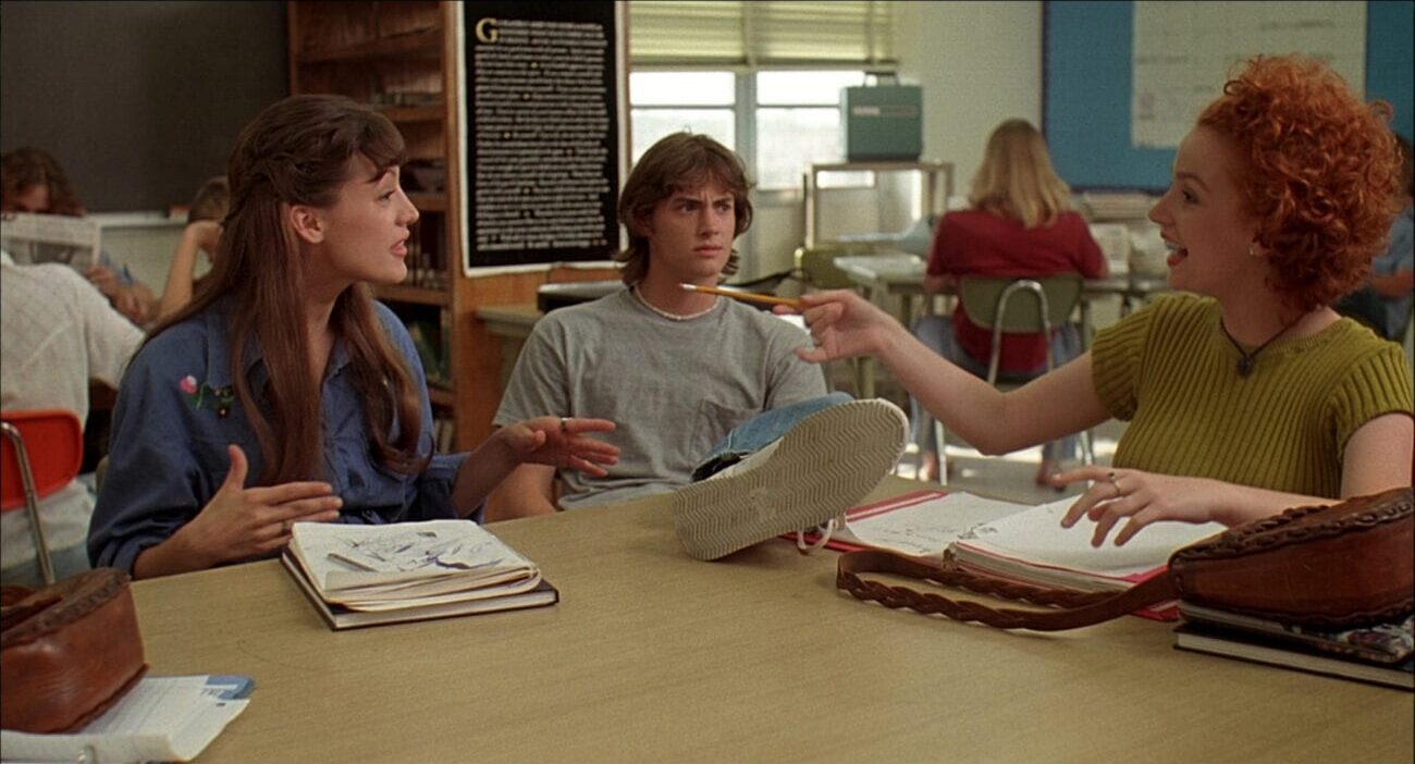 Jodi (Michelle Burke), Pink (Jason London), and Cynthia (Marissa Ribisi) sit in a classroom talking to each other. Pink has his foot on the desk.