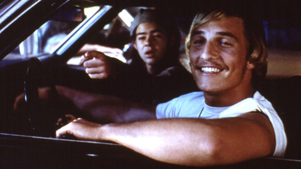 Slater (Rory Cochrane) and Wooderson (Matthew McConnaughey) sit in Wooderson's souped-up car, talking to friends at the Top Notch.