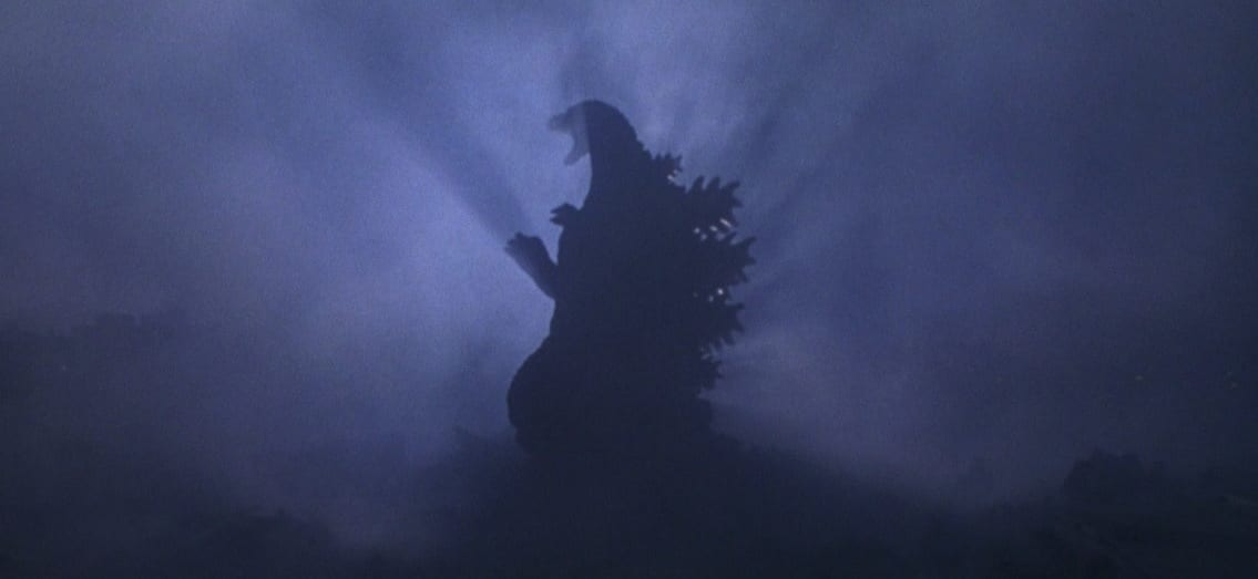 A resurrected Godzilla Junior triumphantly roars while standing in a cloud of smoke