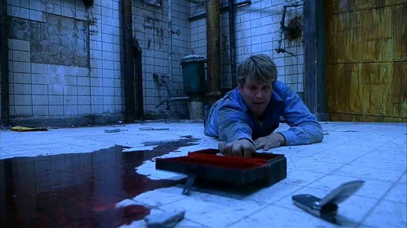 Lawrence Gordon reaching for a cell phone with a pool of blood covering the floor underneath him.