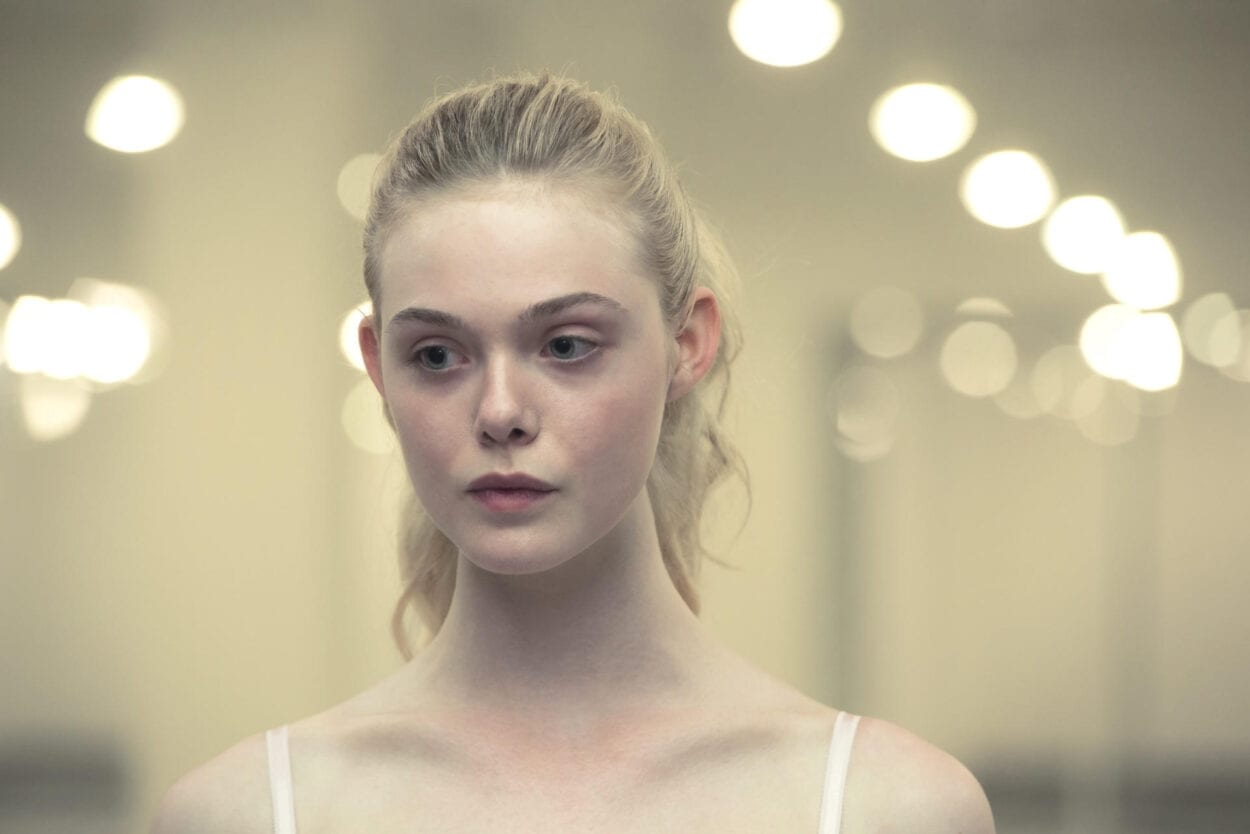 A close up of Elle Fanning as Jesse. She is wearing little or no makeup and has a neautral expression
