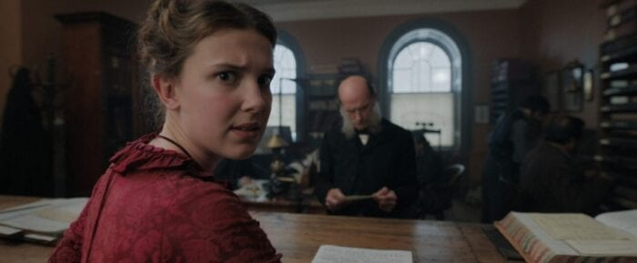 Enola in a red dress turns over her shoulder to give an annoyed look into the camera while a bald man on the other side of the desk in between them stares down at a piece of parchment.