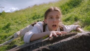 In a field a man in a light tan suit lies be hind a young girl dressed as a boy, grasps a large rock with her mouth agape