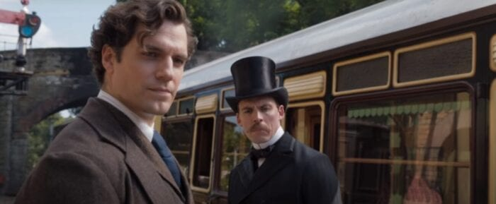 Sherlock and Mycroft stand outside on a train platform on a sunny day, the train beside them. One man in a tweed suit on the left the other in a nice black suit on the right