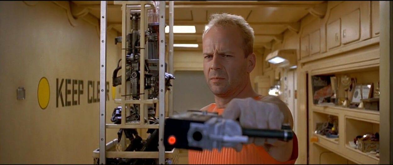 Beuce Willis holding a futuristic gun to the camera