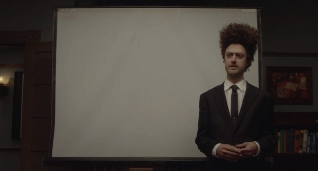 Kirk in an Eraserhead wig in front of a movie screen