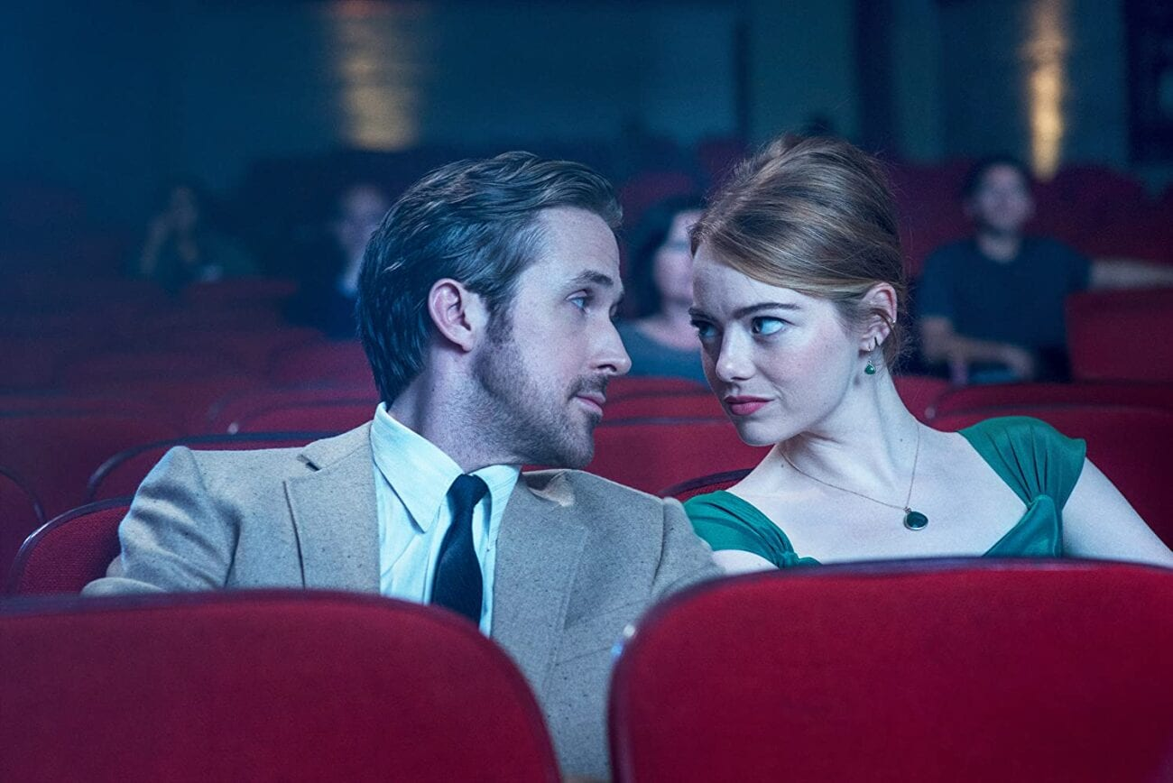 Ryan Gosling and Emma Stone look at each other while sitting in a theater