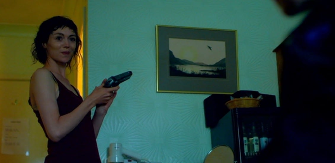Jessica Hyde holding a gun, backdrop is yellow