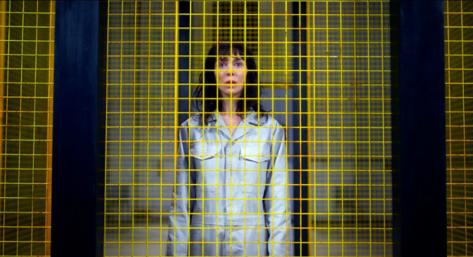 Jessica Hyde stands behind striking yellow bars