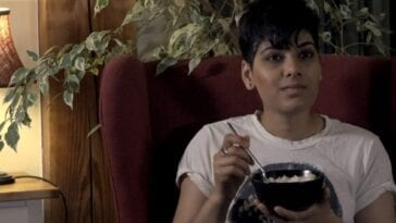 a woman sits in a padded chair in a well lit room smiling at the camera while eating a bowl of rice.