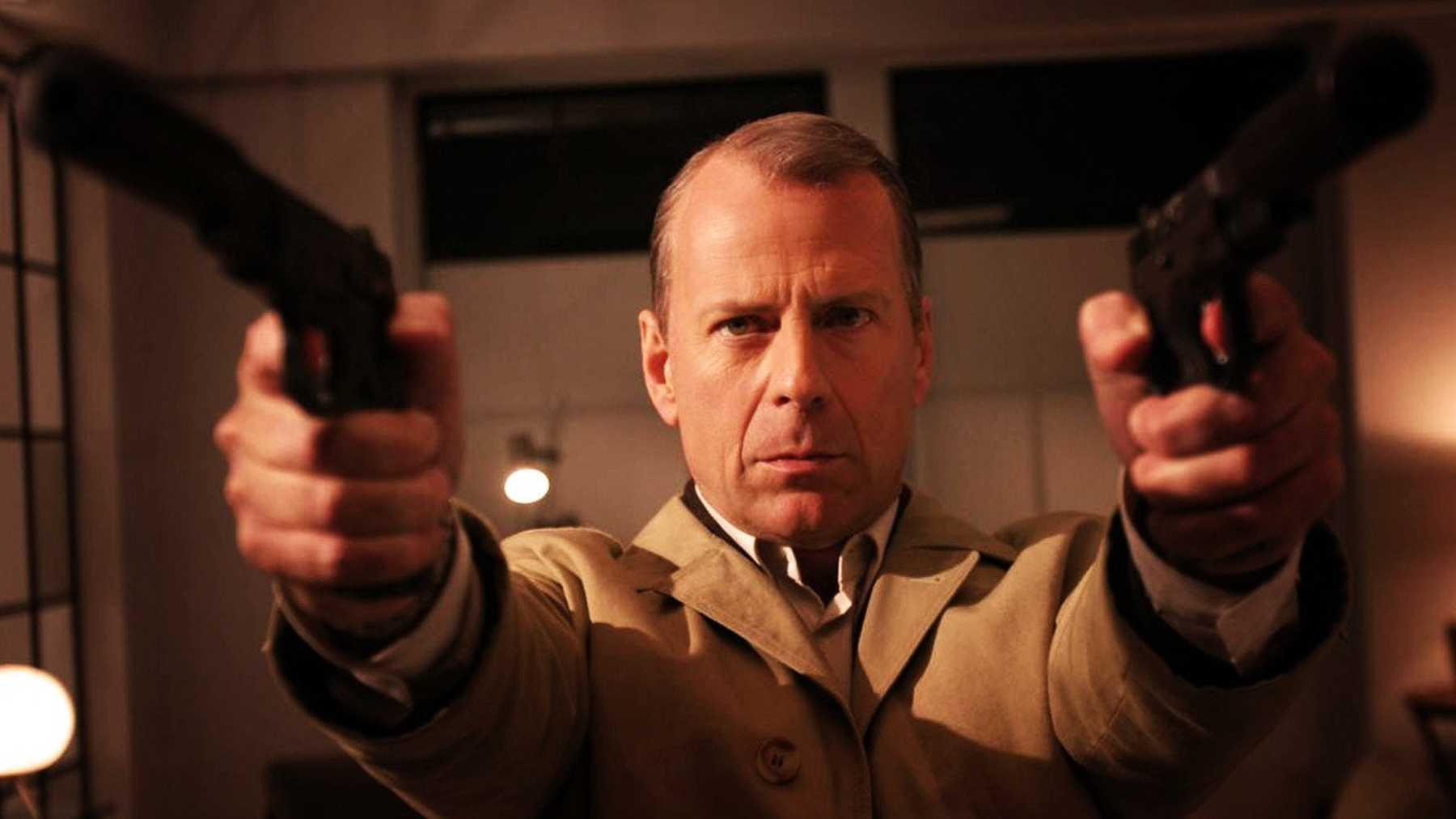 Bruce Willis holding 2 guns to the camera