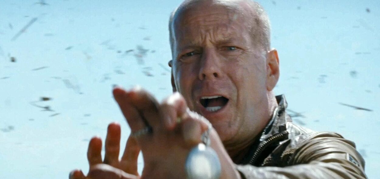 Bruce Willis holding his hands out with grass flying behind him