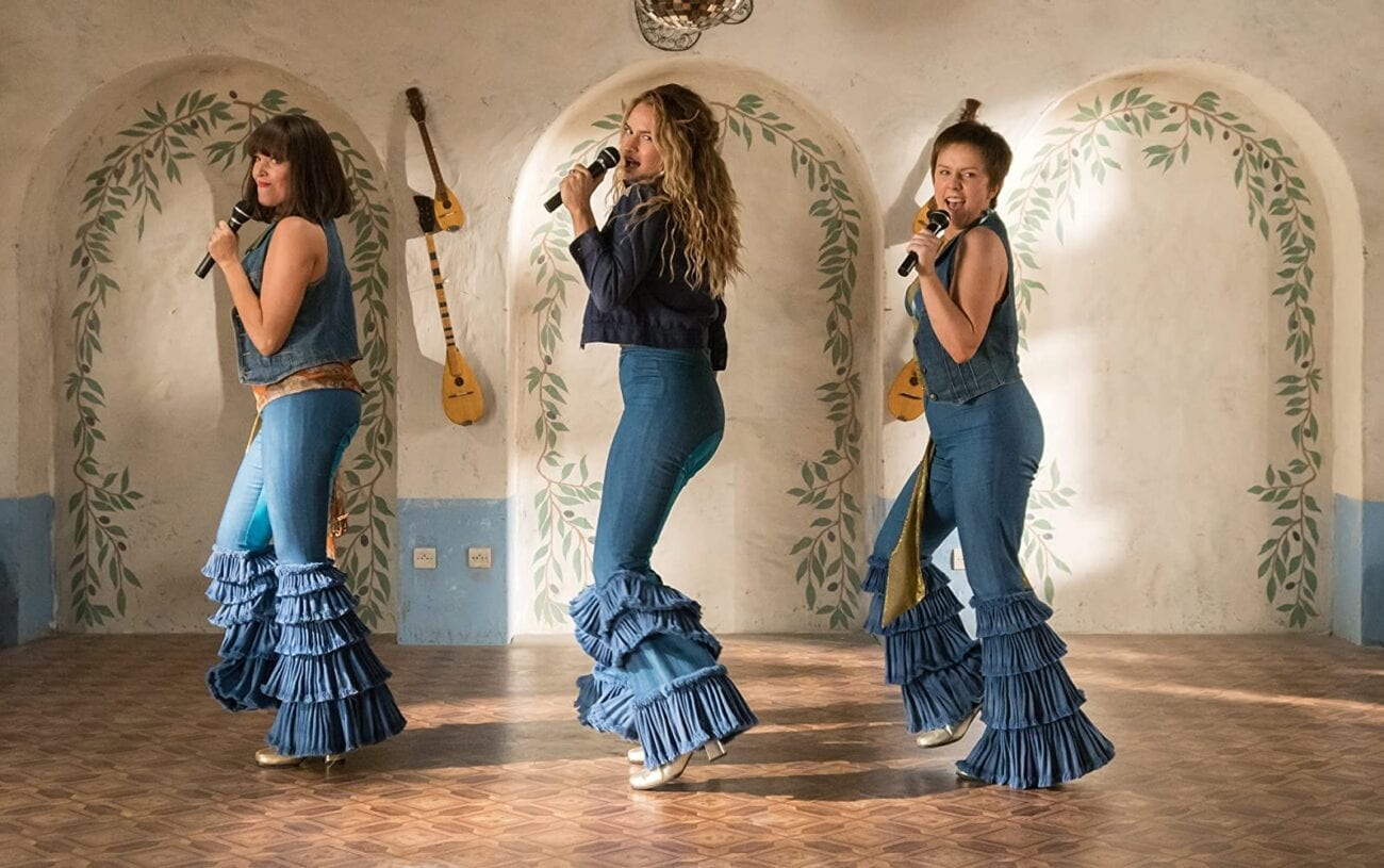 Women dance and sing with microphones while wearing frilly pants