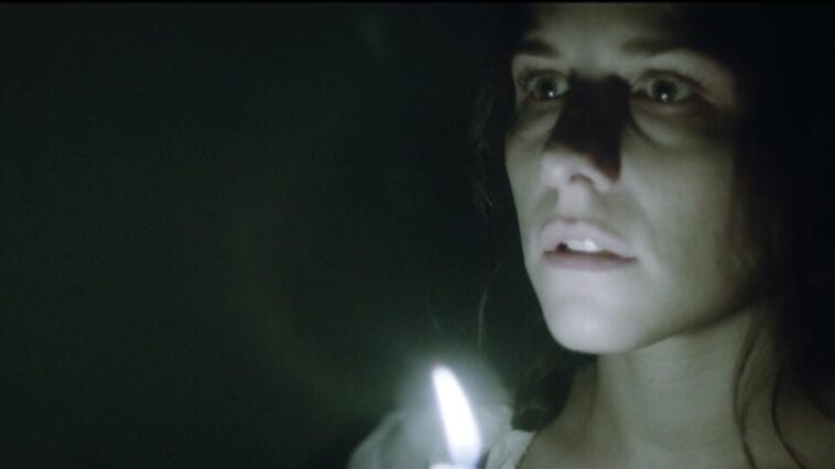 Mary Shelley walks down a dark corridor holding a candle close to her face
