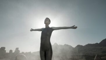 Mother with her arms outstretched standing in front of the sky in Raised by Wolves