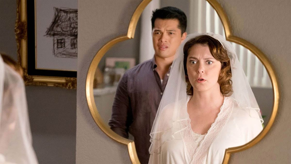 Rebecca and Josh look horrified in the reflection of a mirror