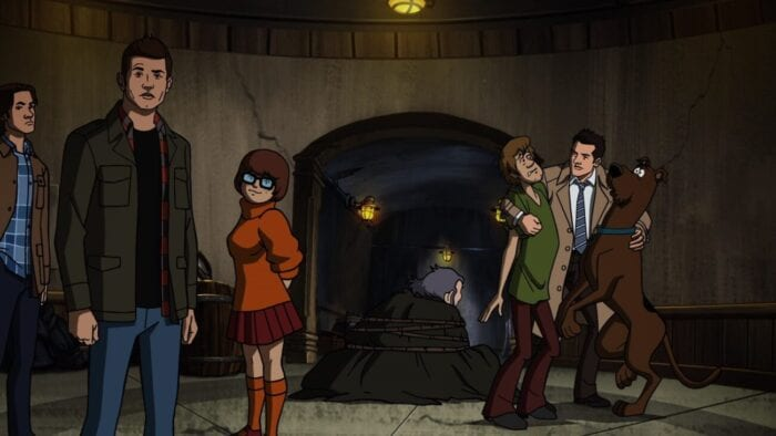 Sam, Dean, and Velma stand on the left looking at the camera, Castiel hugs Shaggy and Scooby on the right, and the unmasked villain sits tied up in the center of a dungeon area