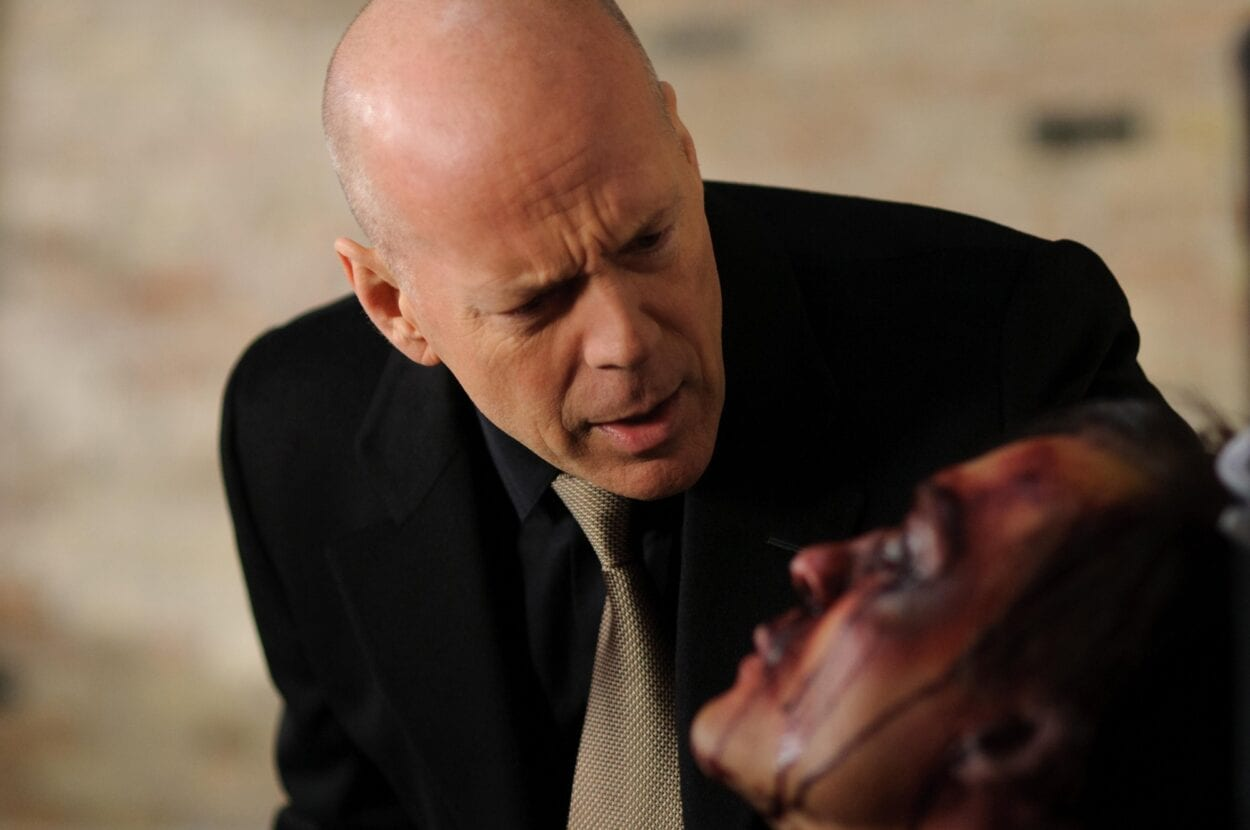 Bruce Willis in a suit standing over a badly-beaten man