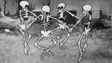 A bunch of cartoon skeletons dance in a graveyard