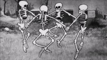 Black and white cartoon image of four skeletons dancing in a circle with joined hands.