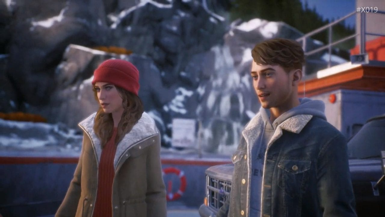 tyler and alyson stand in front of a snowy mountain