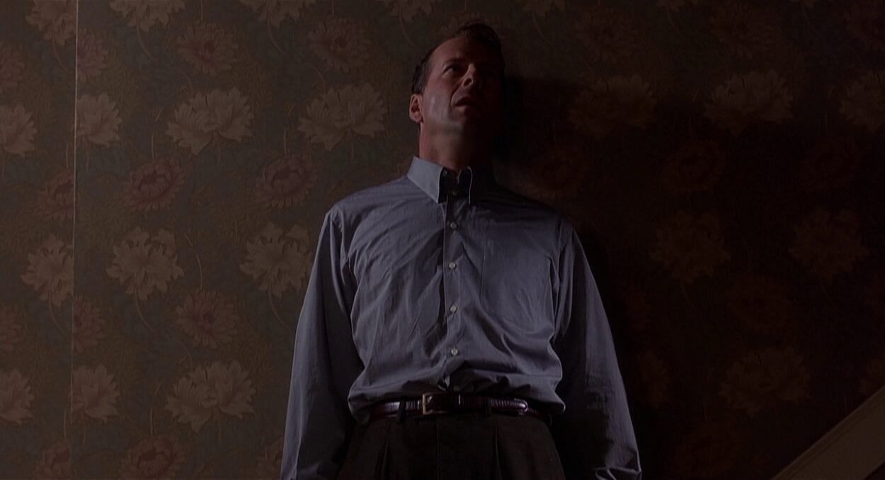 Bruce Willis standing atop the stairs, against the wall
