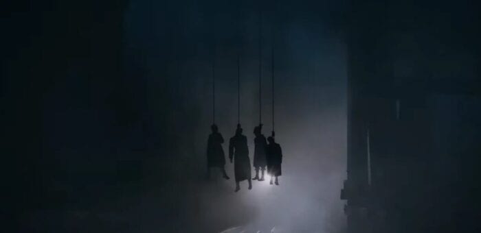 the silhouettes of 4 people hanging by their necks from the above bridge as a train is about to pass through