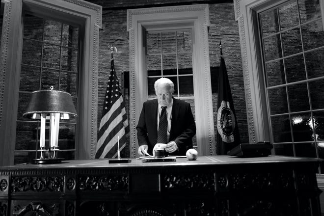 Martin Sheen as an older Jed Bartlet stands behind the desk in the Oval Office in a black and white shot