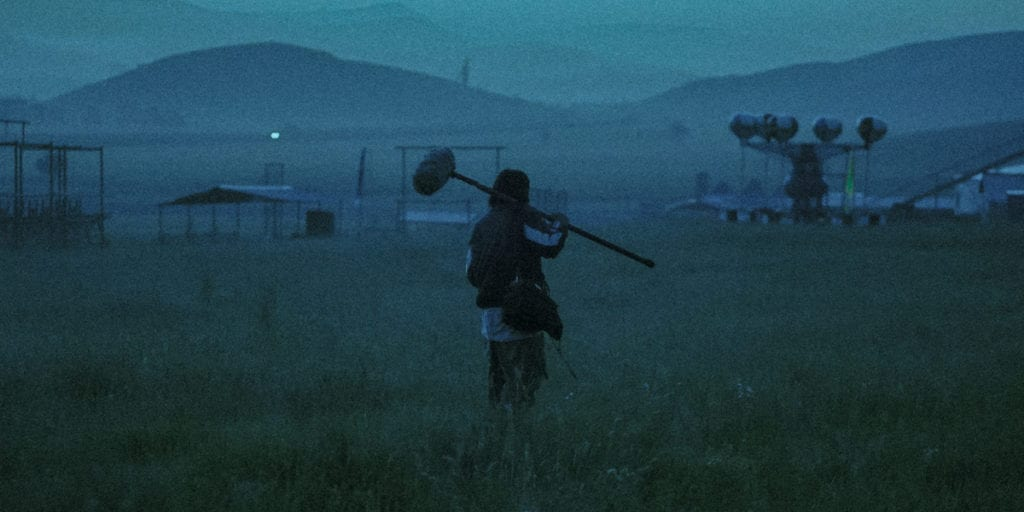 Striding Into the Wind, protagonist Kun, standing in a field with his boom mike