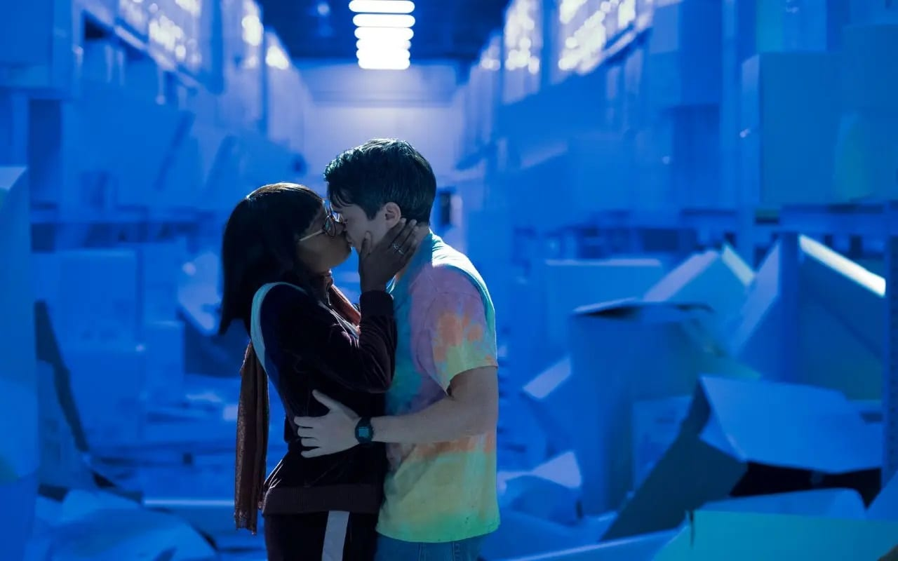 Becky and Ian share a kiss in a warehouse against a blue hue background