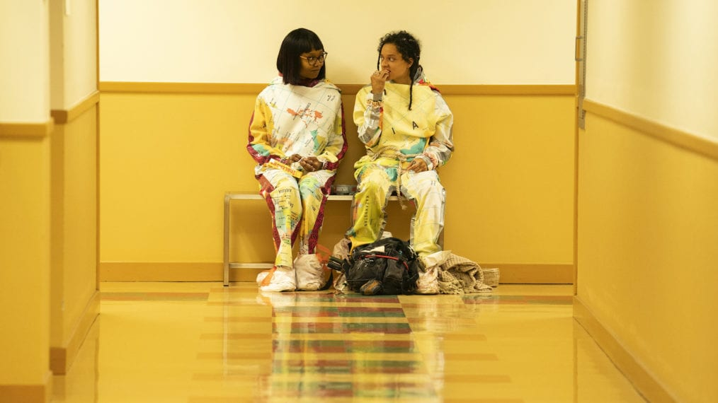 Becky and Jessica sitting in a yellow corridor