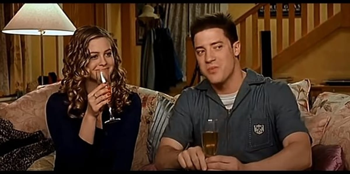 Brendan Fraser and Alicia Silverstone in Blast from the Past, sitting on a couch together and drinking from wine glasses