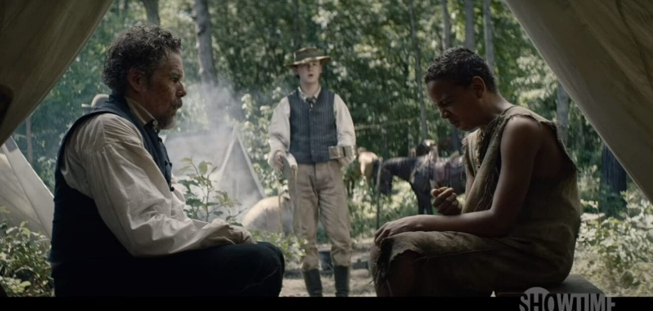 "A shocked John Brown (Ethan Hawke) sitting inside a tent to the left and Henry ""Little Onion"" Shackleford (Joshua Caleb Johnson)making a terrible face after taking a bite from an onion sitting to the right while John Brown Jr. stands in the center between them with cups in his hands."
