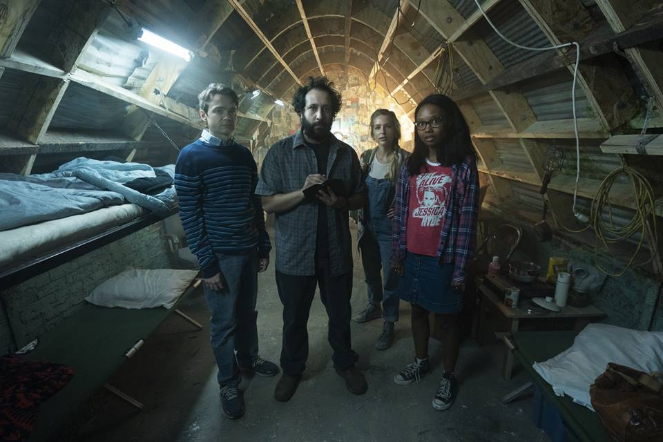 Ian, Wilson, Sam, and Becky stand in Wilson's bunker
