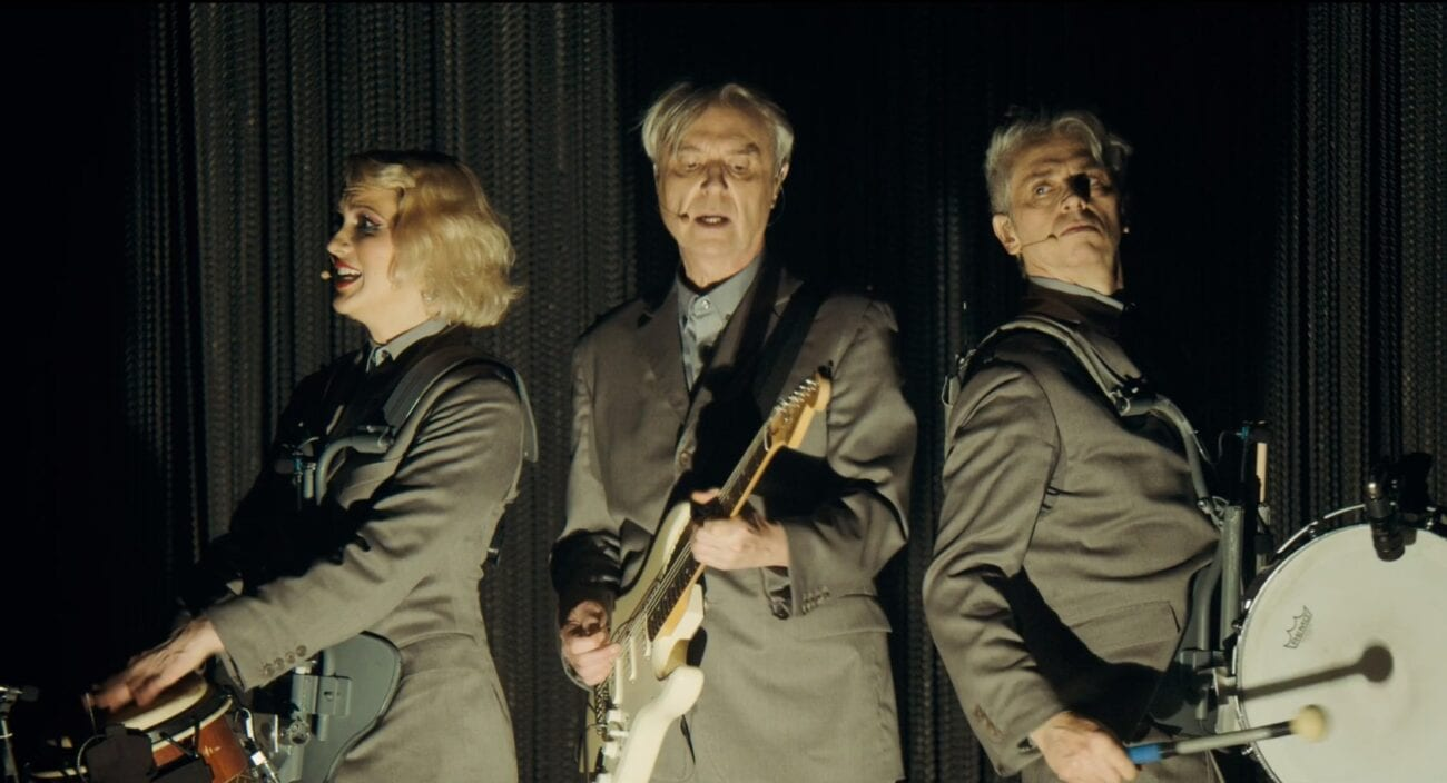 David Byrne plays guitar while flanked by two cast members. They are wearing identical light gray suits.