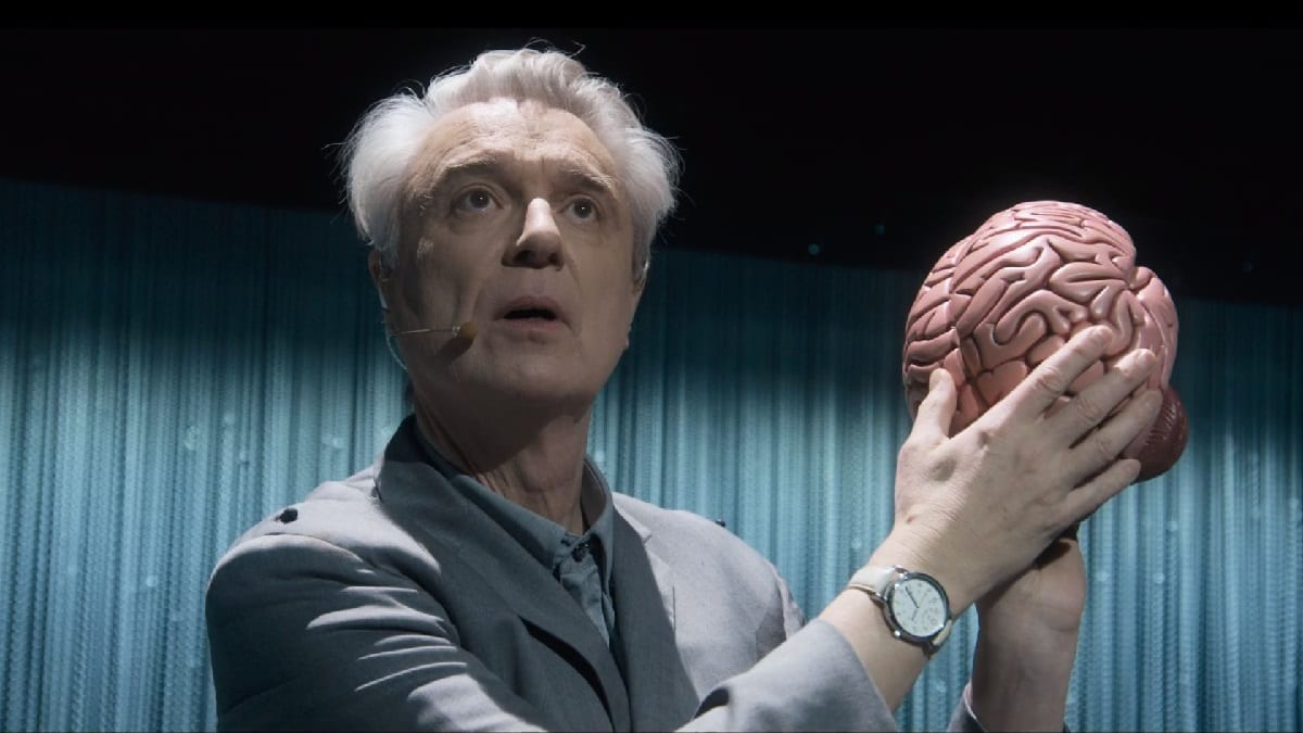 David Byrne looks out to the audience while holding a replica of a brain.