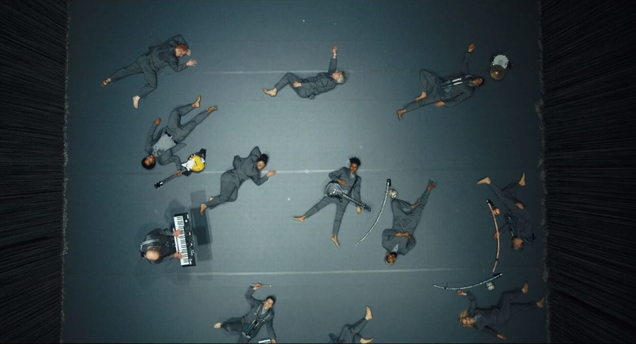 The beginning of I Dance Like This. The cast members lie on the ground as if having been shot. The keyboardist is the only person who is standing. God's view overhead shot