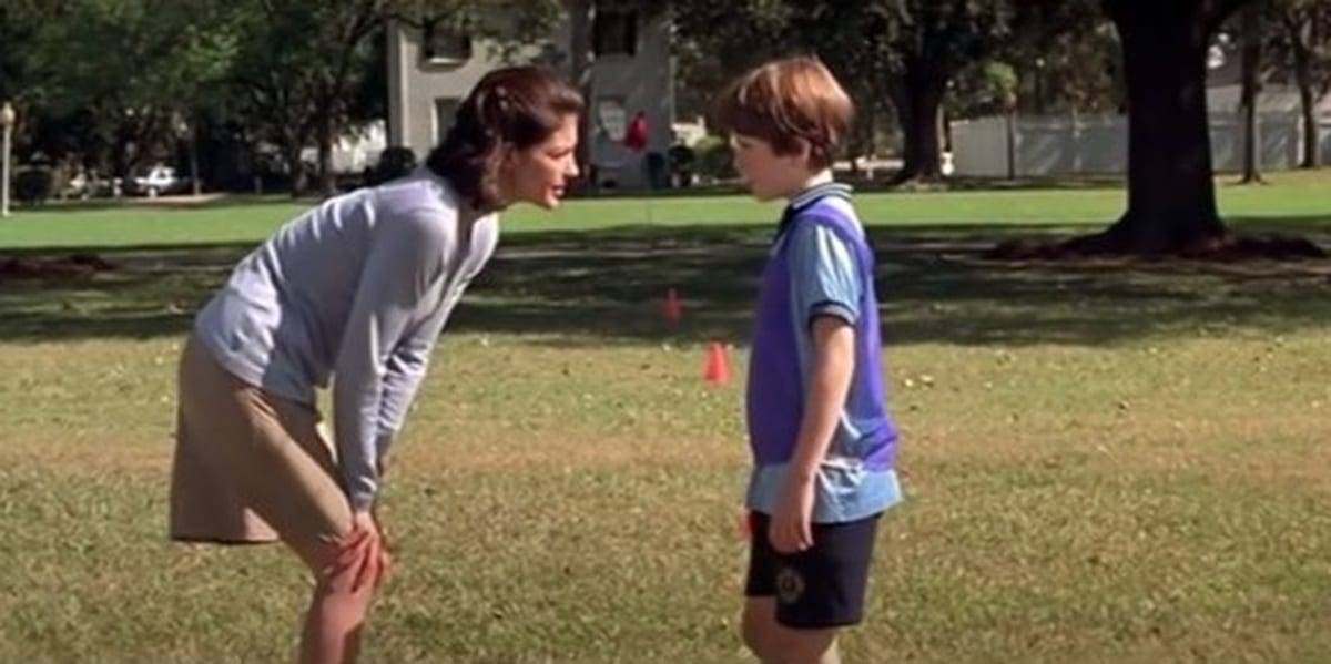 Ashley Judd and her on-screen son in a field, Judd bending slightly to look him in the eyes in Double Jeopardy