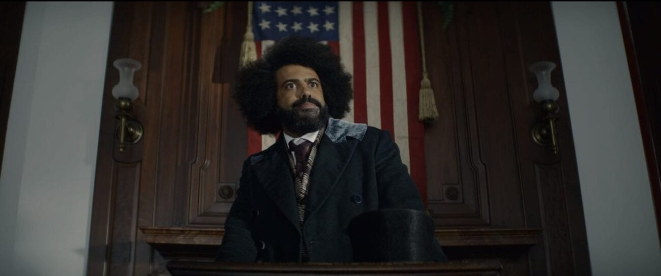 Frederick Douglass (Daveed Diggs) standing in the center of the shot looking off into the distance wearing a black suit with a top hat on a podium in front of him, behind him is a large American flag hanging vertically, a wooden wall is behind the flag with two lamps on either side