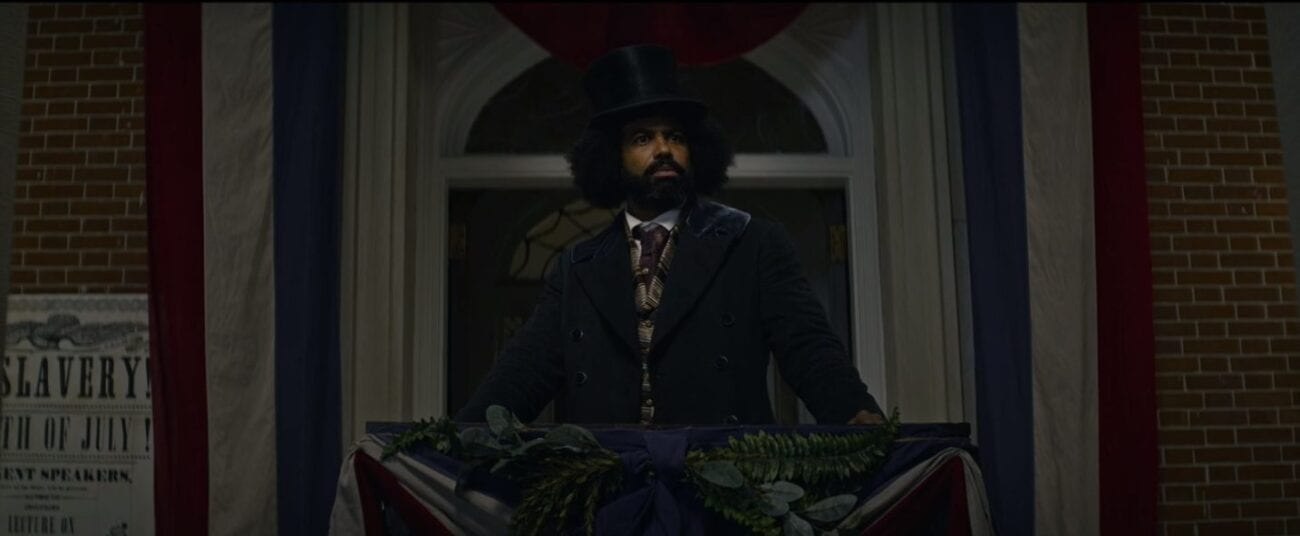 Douglass (Diggs) standing in front of a podium in front of white arched window framed with red, white, and blue drapes, a white anti-slavery poster is on the wall to the left
