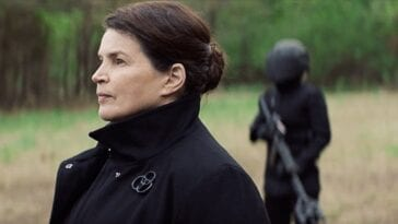 Elizabeth from the CRM stares in the distance with an armed guard behind her