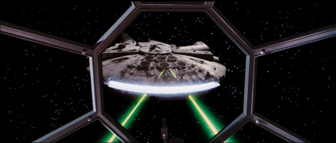 The Millenium Falcon being shot, through the window of a TIE figther