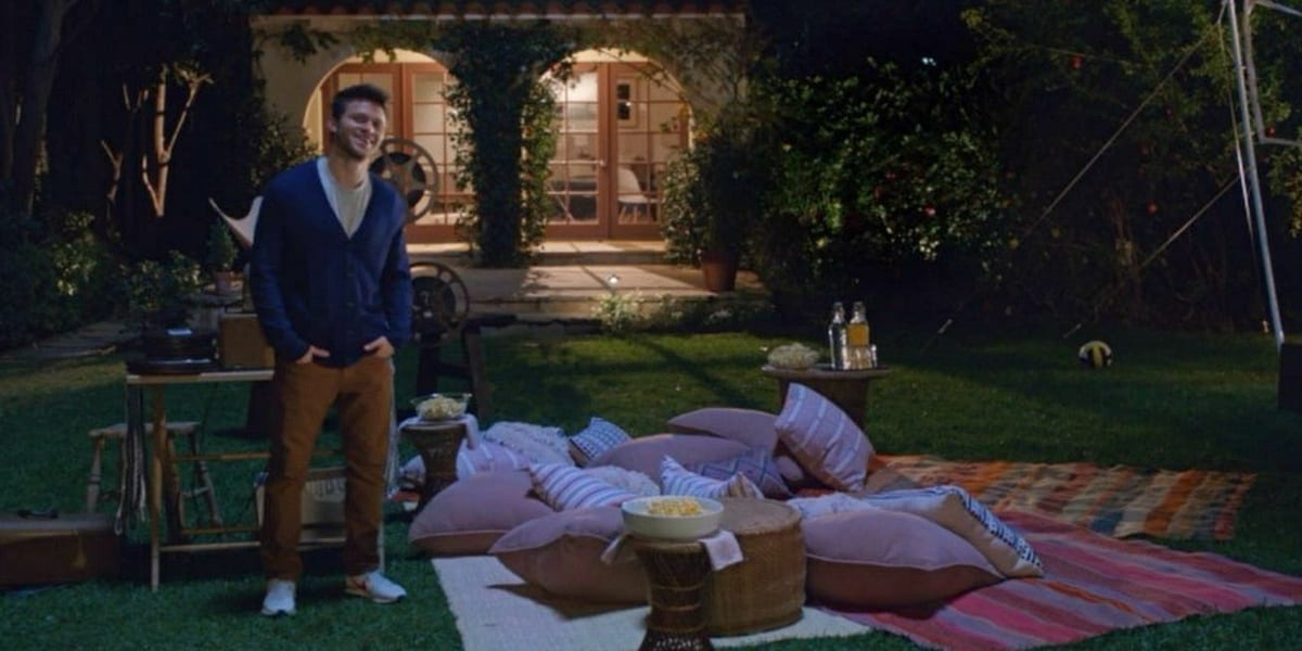 George standing besides a bunch of pillows ready for movie night in Home Again