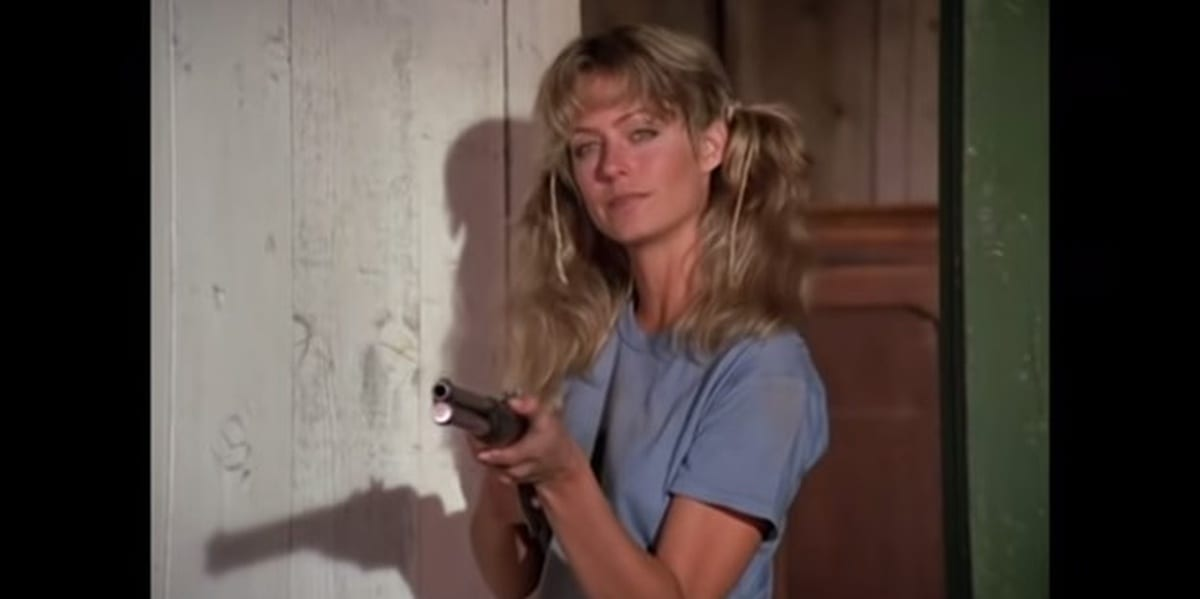 Jill dressed in blue holding a gun in the Charlie's Angels pilot